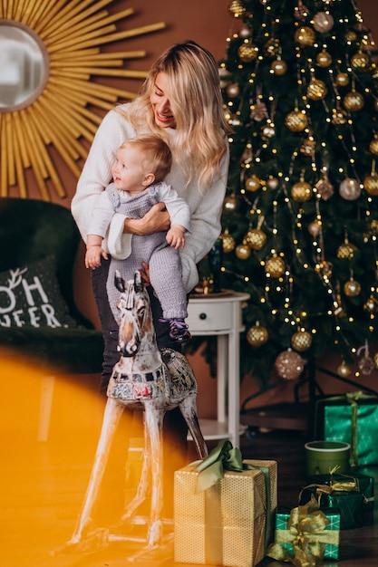 Moeder met schattige dochter zittend op een houten pony door kerstboom Gratis Foto