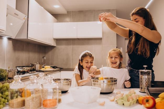 Moeder met twee dochters bij keukenbaksel Gratis Foto