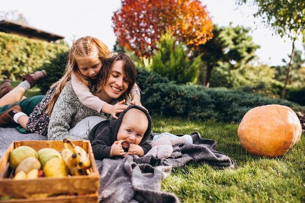 Moeder met twee kinderen met picknick op een achtertuin Gratis Foto