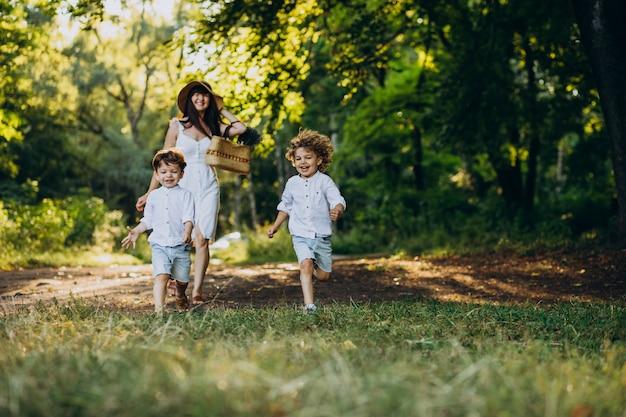 Moeder met twee zonen in park met plezier Gratis Foto