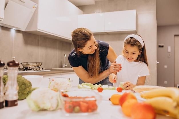 Moeder met weinig dochter die samen bij keuken koken Gratis Foto