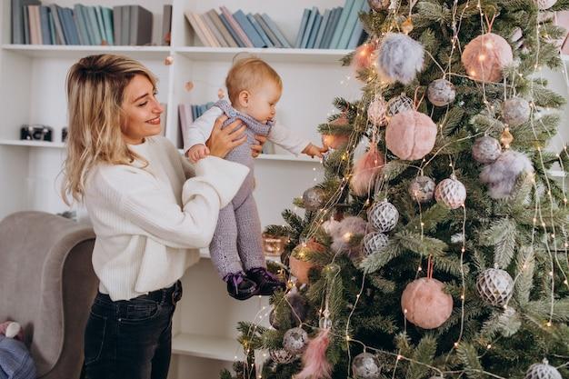 Moeder met weinig dochter hangend speelgoed op kerstboom Gratis Foto