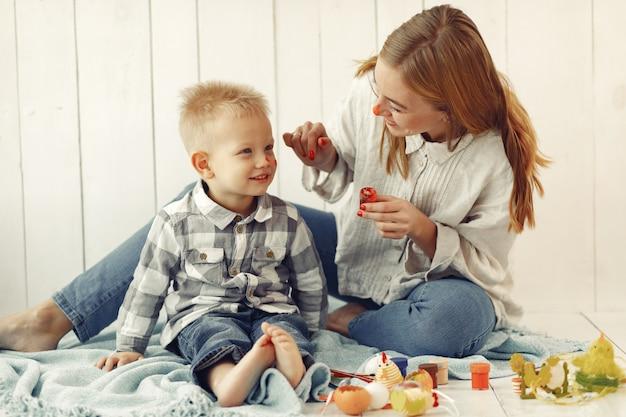 Moeder met zoon die thuis aan pasen voorbereidingen treft Gratis Foto