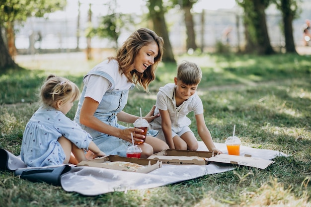 Moeder met zoon en dochter die pizza in park eten Gratis Foto