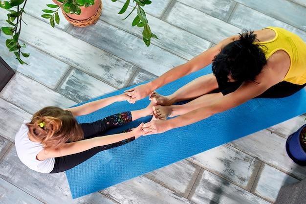Moeder of grootmoeder en haar dochter doen samen gymnastiek- thuis. Premium Foto