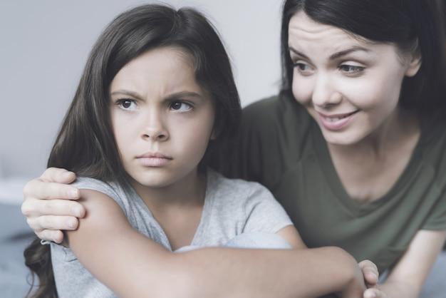 Moeder omarmt onverschillig meisje en glimlach Premium Foto