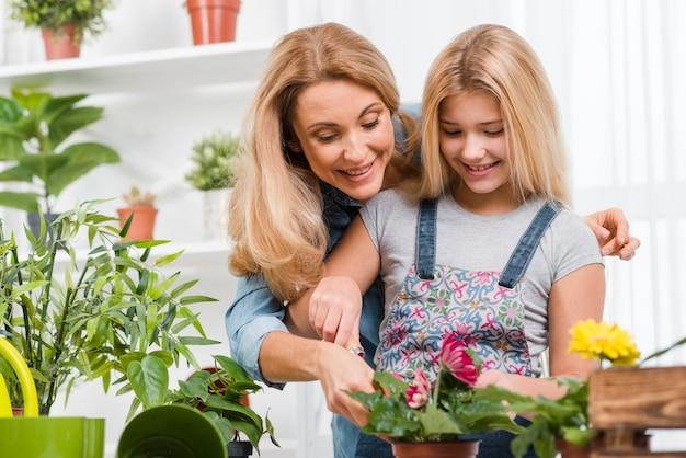 Moeder onderwijs meisje om bloemen te planten Gratis Foto