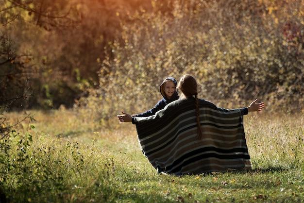 Moeder ontmoet rennende zoon met open armen. uitzicht vanaf de achterkant. herfst bos Premium Foto