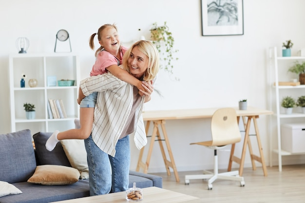Moeder rijdt haar dochter met het syndroom van down op haar rug terwijl ze in de woonkamer spelen Premium Foto