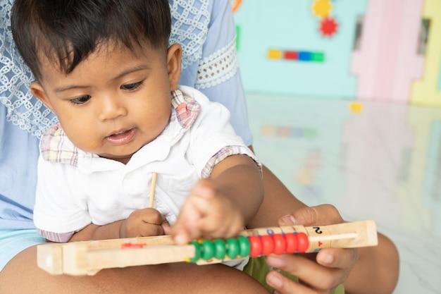 Moeder speelt houten speelgoed met een babyjongen Premium Foto