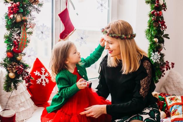Moeder speelt met dochtertje voor een helder raam ingericht voor kerstmis Gratis Foto