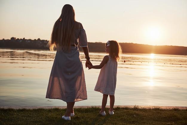 Moeder speelt met haar baby op vakantie in de buurt van de oceaan, silhouetten bij zonsondergang Gratis Foto