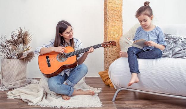 Moeder speelt thuis met haar dochters. lessen over een muziekinstrument, gitaar. het concept van vriendschap en familie van kinderen. Gratis Foto
