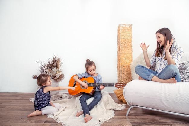 Moeder speelt thuis met haar dochters. lessen over muziekinstrument Gratis Foto