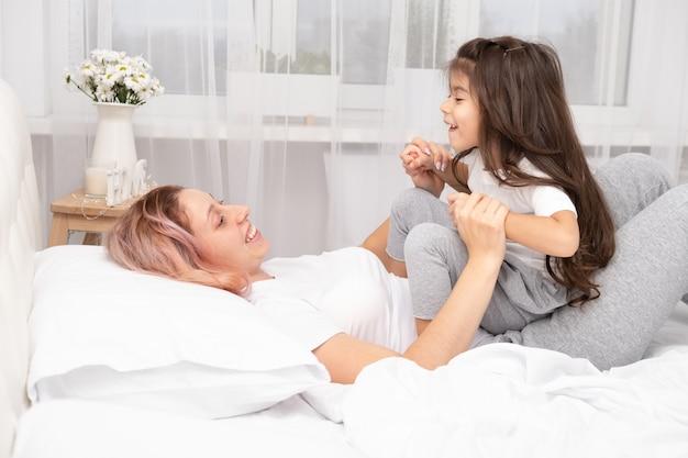 Moeder spelen met actieve dochtertje in bed thuis, plezier, activiteit met kinderen. Premium Foto