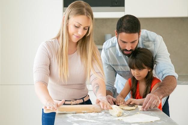 Moeder, vader en dochter kneden en rollen deeg aan de keukentafel met bloempoeder. Gratis Foto