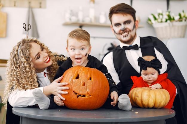 Moeder vader en kinderen in kostuums en make-up. familie bereidt zich voor op de viering van halloween. Gratis Foto