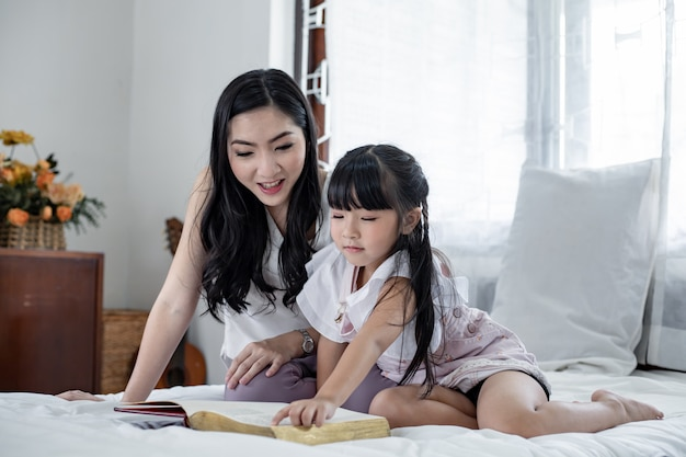 Moeder vertelt haar dochter op het witte bed verhalen. Premium Foto