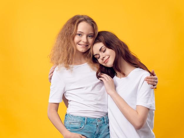 Moederdag, een jonge vrouw met een kind poseren in de studio met bloemen, een geschenk voor vrouwendag en moederdag Premium Foto