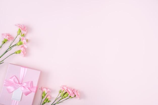 Moederdag, valentijnsdag achtergrondontwerpconcept met roze anjerbloem Premium Foto