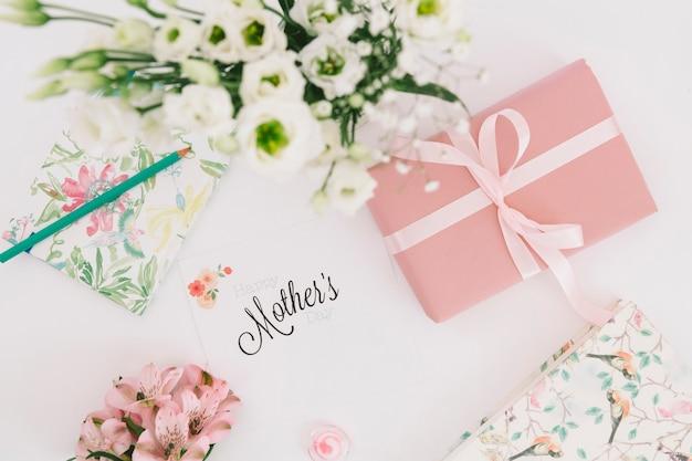 Moeders inscriptie met bloemen en geschenkverpakking Gratis Foto