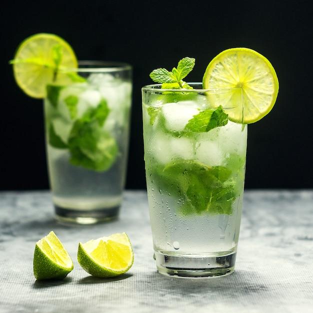 Mojitococktail met limoen en munt in glas op een grijze steen. vierkant Premium Foto