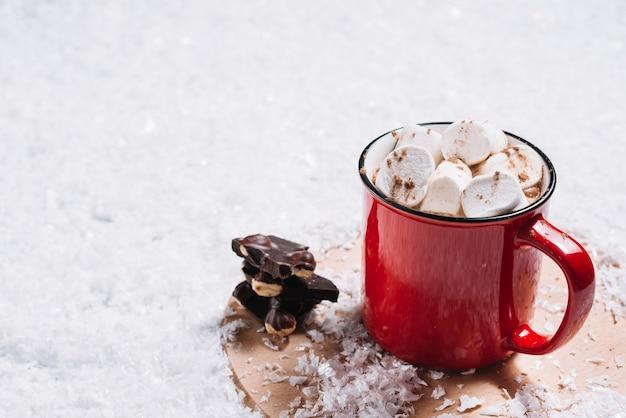 Mok met marshmallows in de buurt van chocolade op staan tussen de sneeuw Gratis Foto