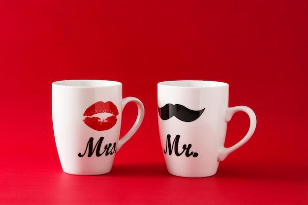 Mokken met snor en lippen voor valentijnsdag op rood Premium Foto