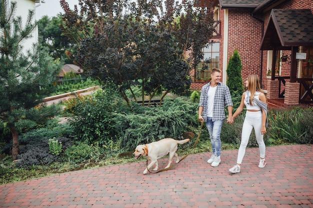 Moment van rust! jonge aantrekkelijke familie die de labrador dichtbij het huis loopt. mooi paar dichtbij modern huis met hond aan de leiband. Premium Foto