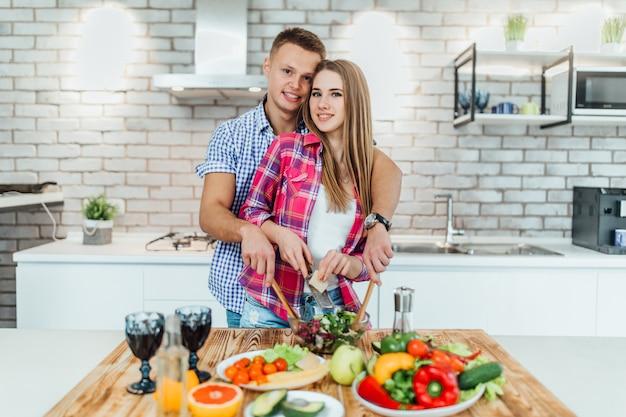 Momenten van intimiteit. mooi jong paar kokend diner bij moderne keuken. Premium Foto