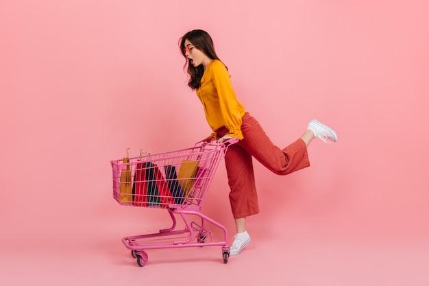 Momentopname van volledige lengte als een meisje shopaholic in een heldere outfit. model draagt supermarktwagen met pakketten. Gratis Foto