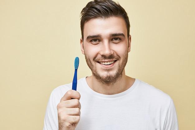 Mondhygiëne en gezond mondgebiedconcept. portret van aantrekkelijke gelukkige jonge man doet ochtendroutine poseren geïsoleerd met tandenborstel, tanden gaan poetsen voor het slapengaan, kijkend met een glimlach Gratis Foto