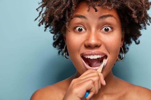 Mondhygiëne en tandheelkunde concept. headshot van verrast jonge afro-amerikaanse vrouw met knapperig haar, tandenborstel en tandpasta gebruikt voor het reinigen van tanden, staart met afgeluisterde ogen geïsoleerd op blauw Gratis Foto