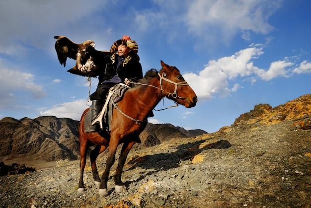 Mongoolse man op een paard met een adelaar Premium Foto