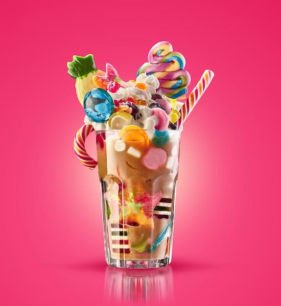 Monster shake, freak caramel shake geïsoleerd. kleurrijke, feestelijke milkshake-cocktail met snoepjes, gelei. gekleurde karamelmilkshake met verschillende kindsnoepjes en lekkernijen in glas. zoete milkshake Premium Foto