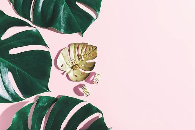 Monstera groene bladeren met kantoorsteunen op roze Gratis Foto