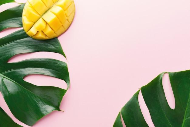 Monstera groene bladeren met mango op roze Gratis Foto