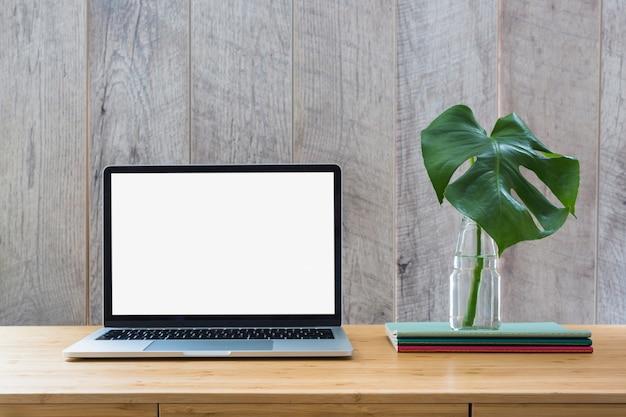 Monsterablad in glasfles over de boeken en laptop met het witte scherm Gratis Foto