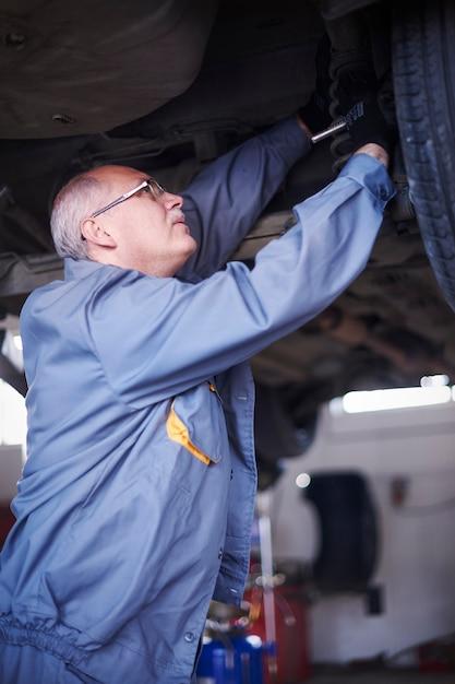 Monteur die een auto in de werkplaats herstelt Gratis Foto