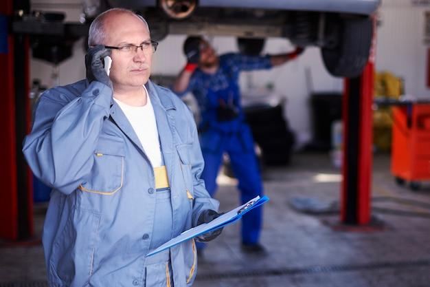 Monteur in gesprek met een klant in de werkplaats Gratis Foto