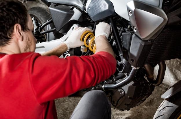 Monteur reparateur doet onderhoud of reparatie, reparatie op de motorfiets, motor, servicecentrum Premium Foto