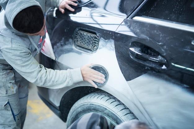Monteur werknemer reparateur schuren polijsten carrosserie en auto voorbereiden schilderij in werkplaats garage Gratis Foto