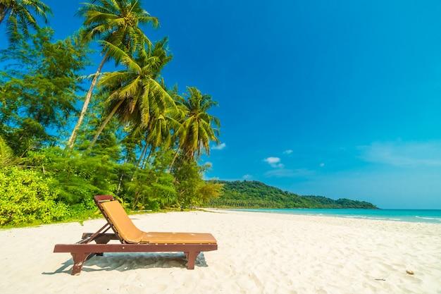 Mooi aard tropisch strand en overzees met stoel en kokosnotenpalm op paradijseiland Gratis Foto