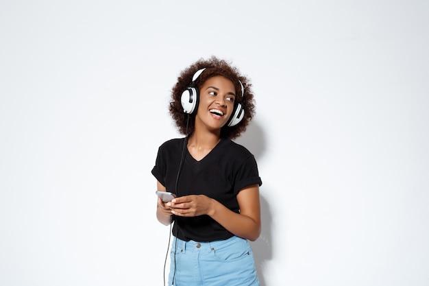 Mooi afrikaans meisje luisteren muziek in hoofdtelefoons over witte muur Gratis Foto