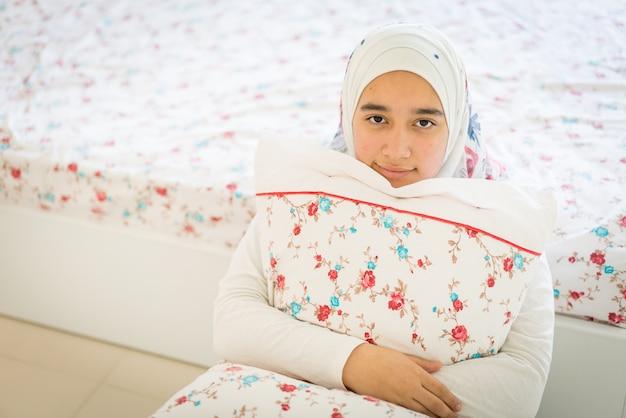 Mooi arabisch meisje op bed in moderne slaapkamer foto premium