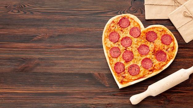 Mooi arrangement voor valentijnsdag diner met hartvormige pizza en kopie ruimte Gratis Foto
