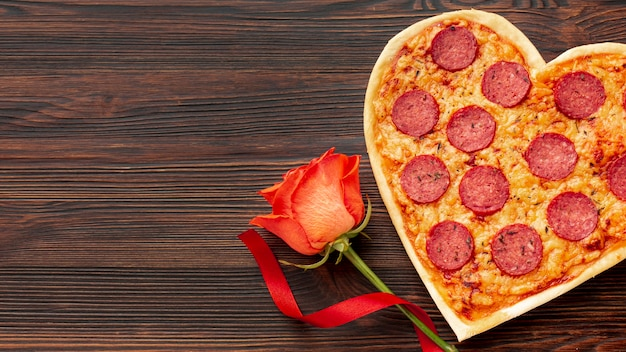 Mooi arrangement voor valentijnsdag diner met hartvormige pizza en roos Gratis Foto