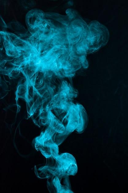 Mooi blauw rookpatroon dat op zwarte achtergrond wordt uitgespreid Gratis Foto