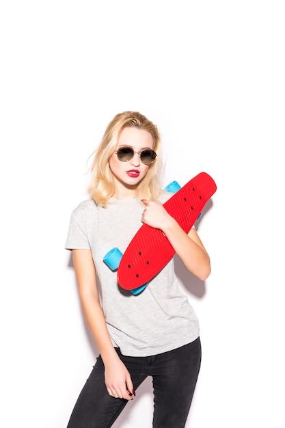 Mooi blodnie skater meisje in schitterende zonnebril blijft voor witte muur Gratis Foto