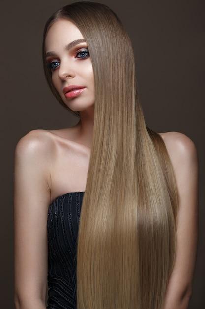 Mooi blond meisje met een perfect glad haar, klassieke make-up. mooi gezicht Premium Foto